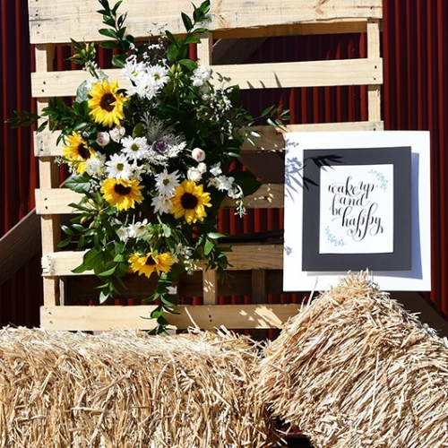 floral spray displayed on wooden pallet with hay bale