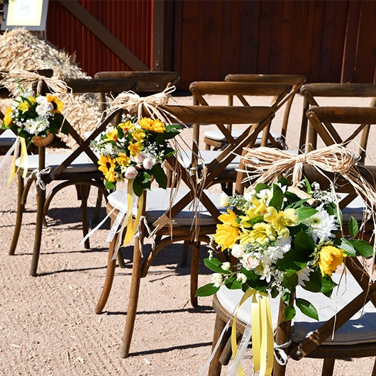 handle baskets on chairs in aisle at wedding