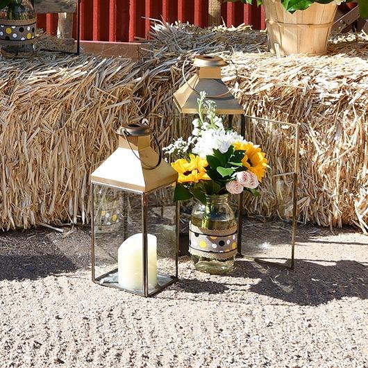 mason jar with flowers next to lantern